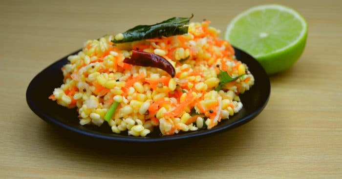 carrot kosambari in black plate with half lime on wood table