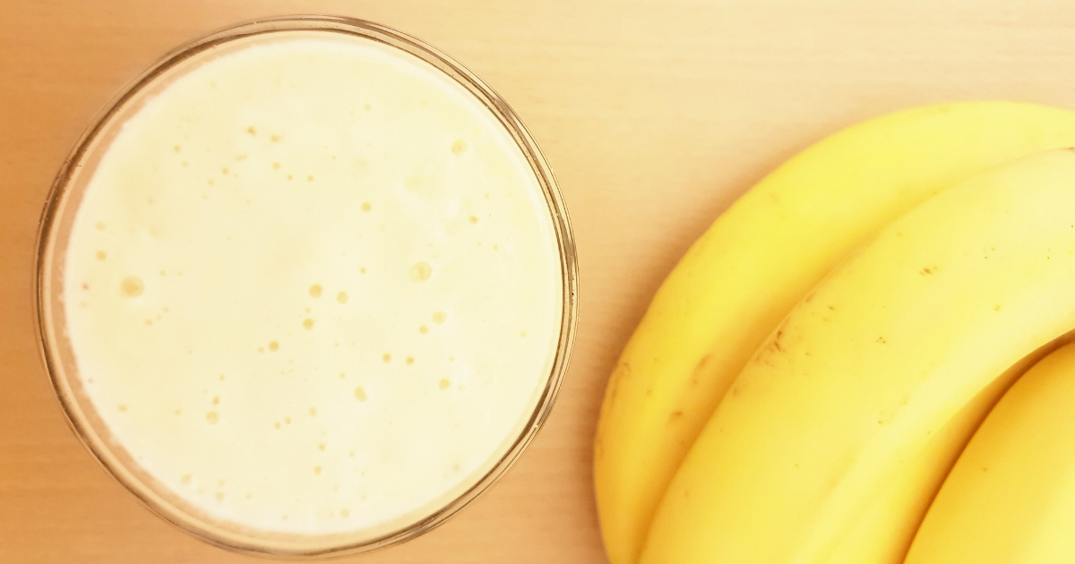 glass of smoothie and banana on table