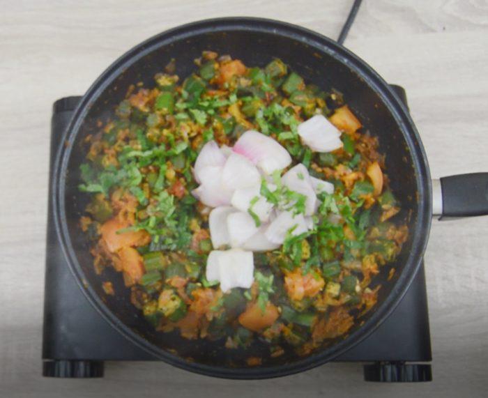 mixing in onion, coriander and lemon juice to bhindi do pyaza.