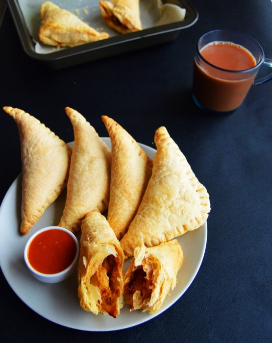 curry puffs with dipping sauce in a plate.