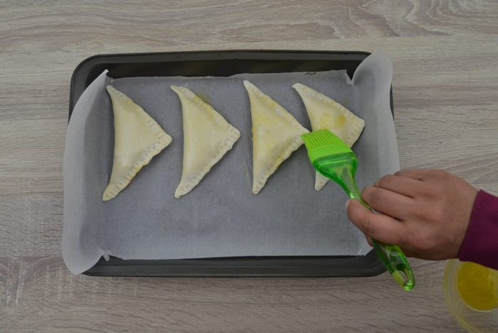 applying melted butter on each curry puff before baking.