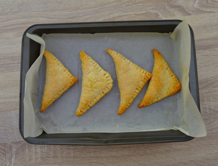 4 baked curry puffs in baking tray.